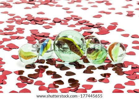 Toy marbles on white background, surrounded by so many red hearts. - stock photo