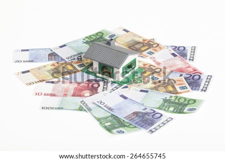 toy model house on a white background with euro banknotes. financial concept for buying  or building real estate - stock photo