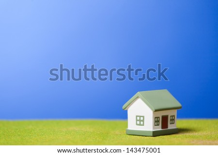 Toy model house on green grass. Conceptual image - stock photo