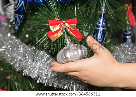 toy on the Christmas tree in a child's hand for the New Year - stock photo