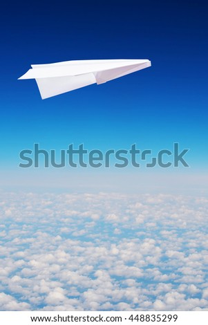 Toy paper plane flies high in the sky over clouds