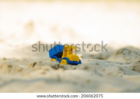 Toy plastic truck on the sand in the sandbox - stock photo