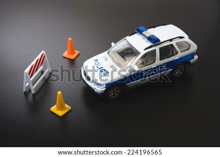 Toy police car and traffic cones, close-up - stock photo