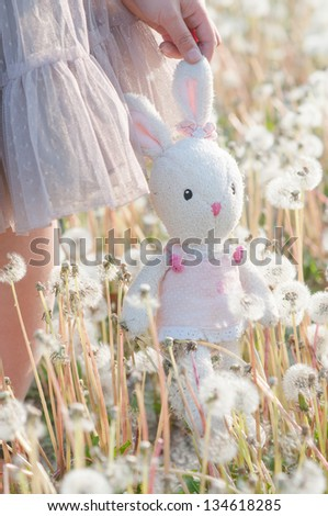 toy rabbit with dandelion in the park - stock photo