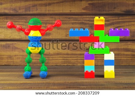 Toy robots made from toy plastic colorful details on wooden background  - stock photo