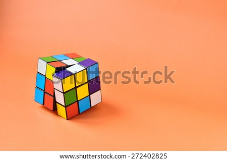 Toy rubik cube  on orange background - stock photo