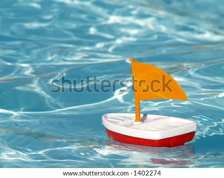toy sailboat in a swimming pool - stock photo