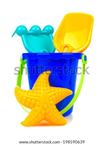 Toy sand pail with rake, shovel and starfish over a white background - stock photo