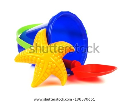 Toy sand pail with shovel and starfish over a white background - stock photo