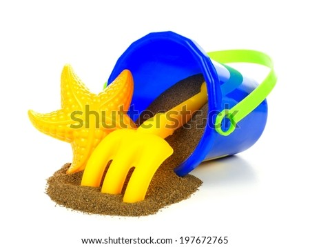 Toy sand pail with spilling sand over a white background - stock photo