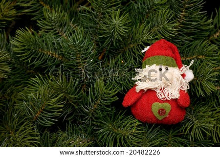 toy Santa Claus against a Christmas tree - stock photo