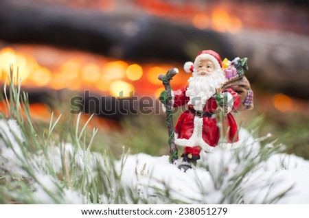 Toy Santa Claus standing on the fir tree branch against the fire background. - stock photo