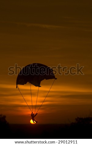 Toy soldier Parachute falling into setting sun - stock photo