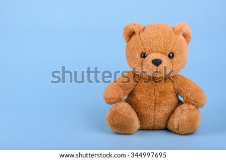 Toy teddy bear on blue background with copy space