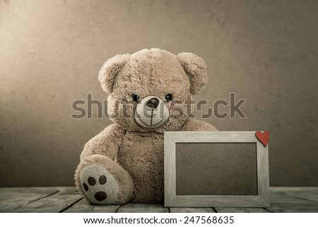 toy teddy bear with wooden photo frame with Valentine's symbol - stock photo