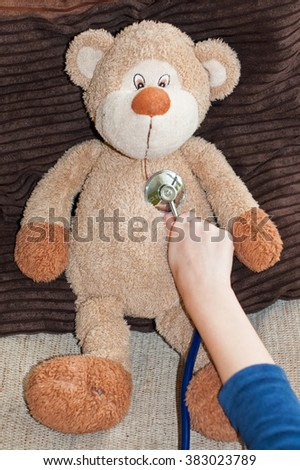 Toy teddy examined by a boy with a stethoscope - stock photo
