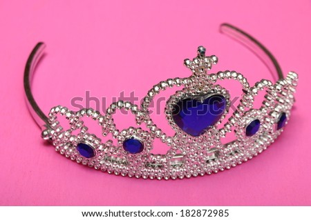 Toy tiara with diamonds and blue gem, like a princess crown on pink background - stock photo