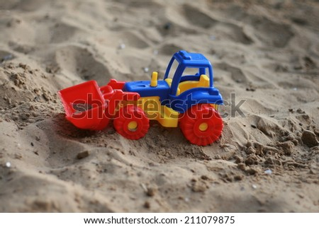 toy tractor on the sand beach summer vacation wheel plastic bucket - stock photo