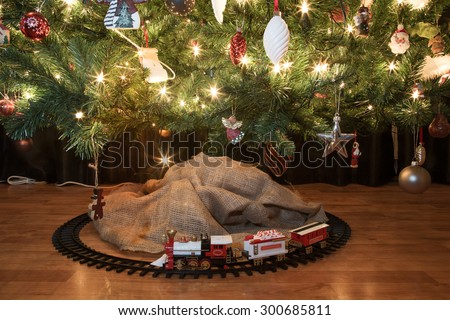 Toy train beneath a decorated christmas tree with christmas lights. starburst forming on lights - stock photo