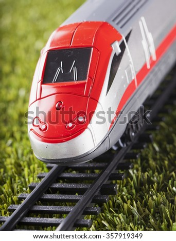 Toy train over railway, close up, vertical image - stock photo