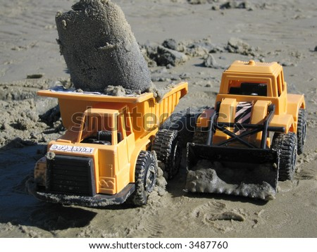 Toy trucks that have been working in the sand
