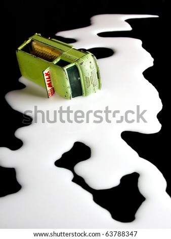 toy van in puddle of spilled milk - stock photo