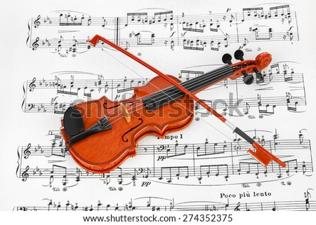 Toy violin and music sheet - art musical background - stock photo