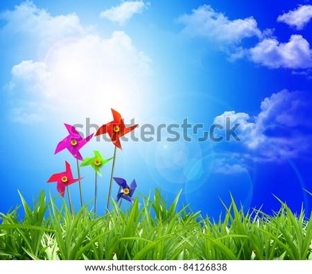 Toy wind turbine at flower summer field - stock photo