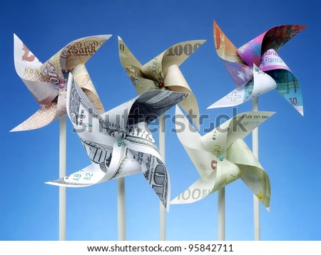 Toy windmills cut from five major world currency banknotes over blue sky - stock photo
