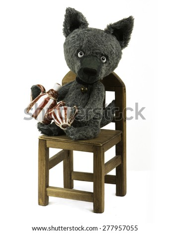 Toy wolf  is sitting on a chair holding a teapot and cup - stock photo