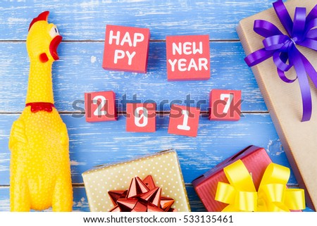 Toy yellow shrilling chicken, Present gift box and Happy new year 2017 number on red paper box cubes on blue wooden background with copy space.Year of the Cock.2017 New Year concept background.