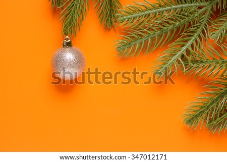 Toys and spruce branches on an orange background - stock photo