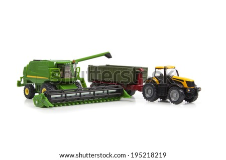 toys combine harvester and tractor with semi-trailer are isolated on white background - stock photo