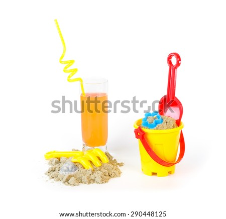 Toys for sand castles and a refreshing drink against a white background - stock photo