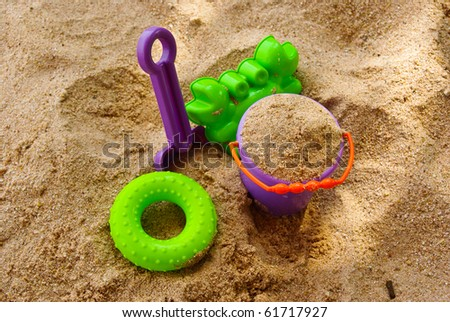 Toys in the sand - stock photo