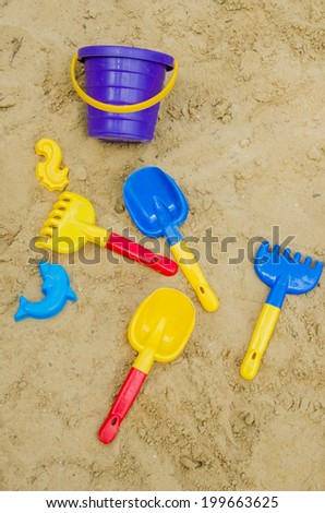 Toys in the sand - shovel, stencils, rakes | vertically - stock photo