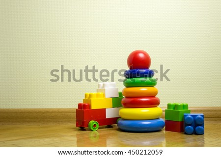 Toys, kids, childhood. Pyramid build from colored wooden rings. Toy for babies and toddlers to joyfully learn mechanical skills and colors. Studio shot at home background.