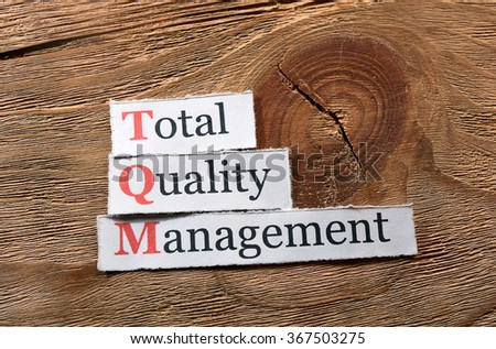 TQM total quality management on paper on wooden background
