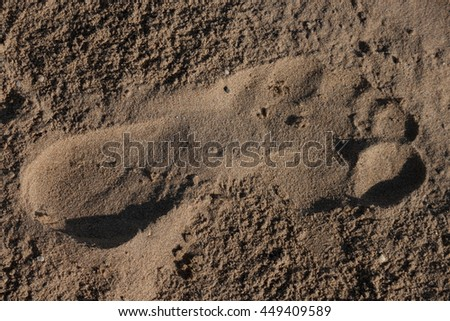 Trace a bare foot on the sand - stock photo