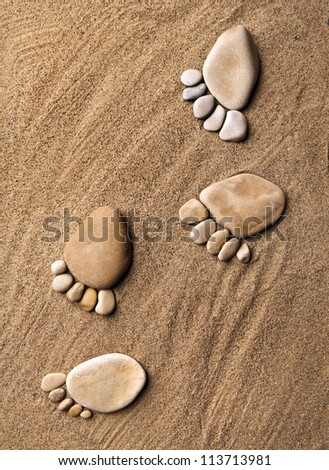 trace feet steps of a pebble stone walking on the sea sand backdrop top view surface  - stock photo