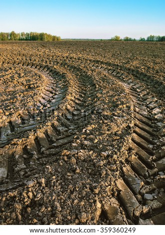 Trace of a tractor on a plowed field - stock photo