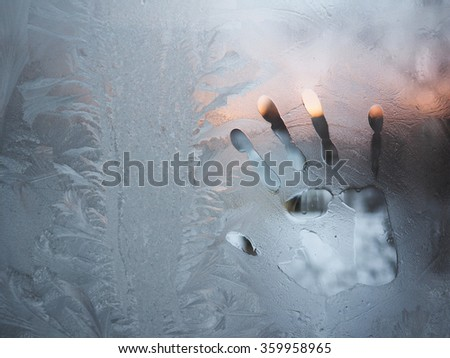 trace their hands on a frozen glass - stock photo