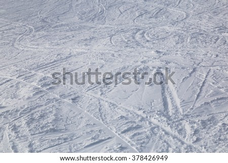 Traces from skiing on white snow close-up. Ski slopes.