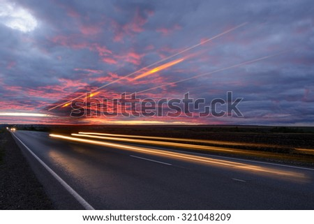 Traces from the car headlights at sunset - stock photo