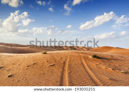Traces in desert Wahiba in Oman with clouds on blue sky - stock photo