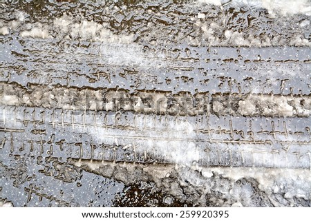 Traces of a vehicle on the dirty melted snow on asphalt background - stock photo