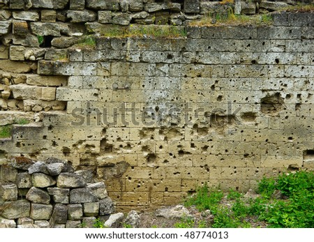 Traces of bullets on fortress wall. Bullet hole background. - stock photo