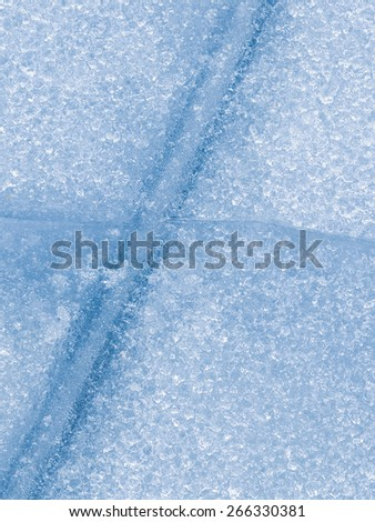 traces of runners at the clear blue brittle ice on the lake in winter - stock photo