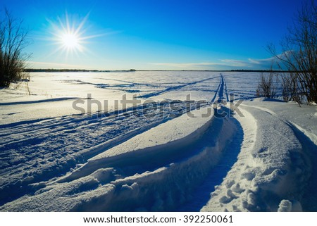 Traces of snowmobiles on the snow in the field . - stock photo