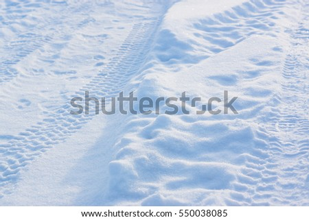 Traces on the snow in a sunny day on winter